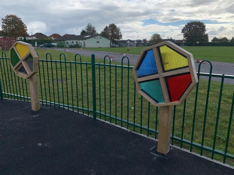 Two sensory spinners with red, yellow, blue and green textures on installed onto black tarmac in front of the green fence with a field on the other side of the fence.