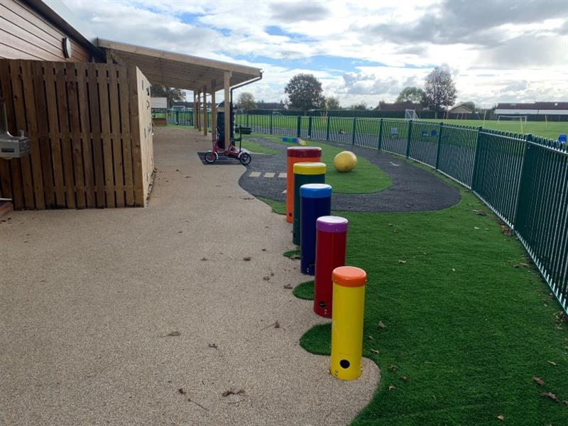 Yellow, red, blue, green and orange African drums placed in height order with yellow being the smallest, installed close to the storage boxes and wetpour roadway.