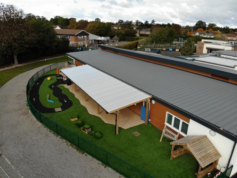 Aerial view of school playground including a timber canopy attached to the school building, artificial grass, get set go blocks, giant playhouse and roadway feature