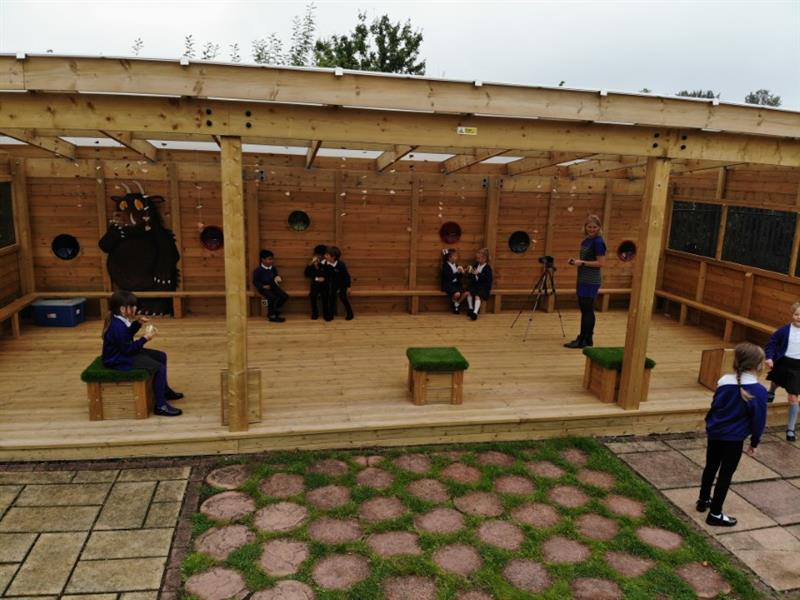 Children sitting inside the new outdoor classroom socialising and eating lunch