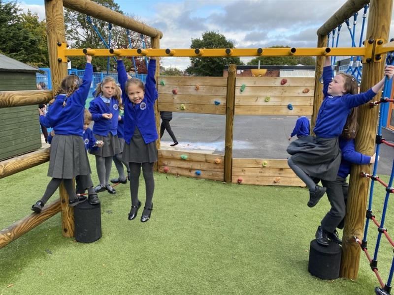 Children hanging from a set of yellow monkey bars
