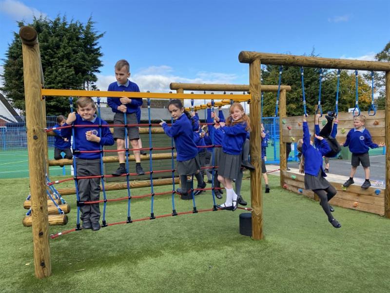 A class of children climbing on a playground climbing frame
