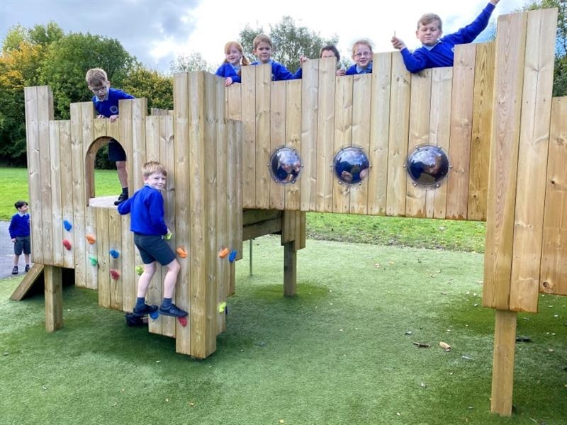 Children standing on top of a playground castle