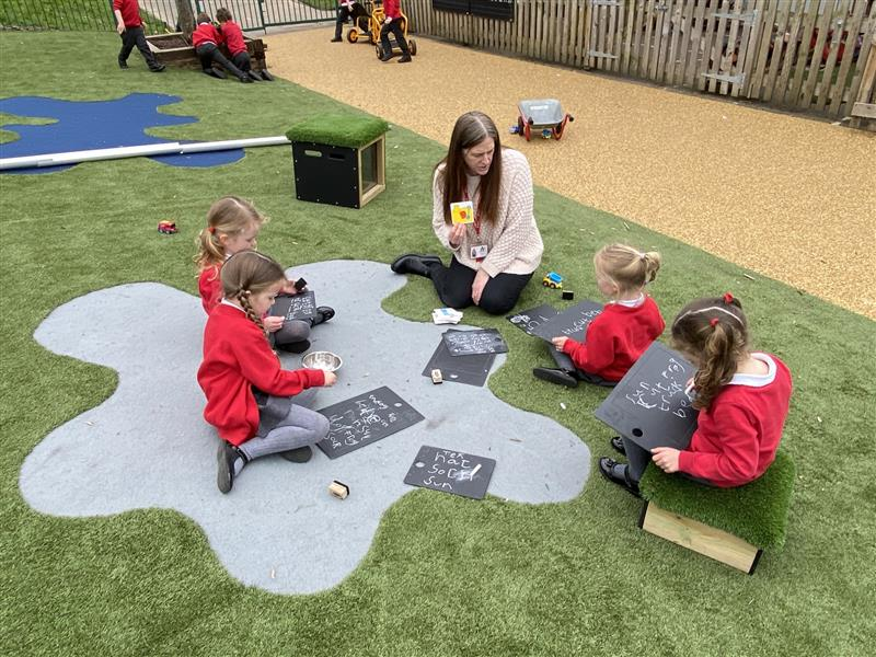 4 children sat on saferturf surfacing participating in a phonics lesson using scribble boards