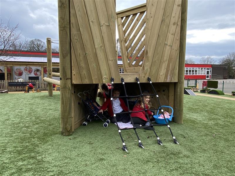3 children hiding under the climbing frame platform playing imaginative play games