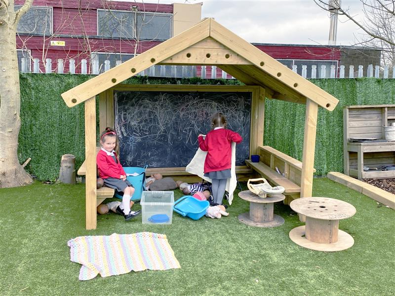 2 children playing inside a giant playhouse with chalkboard, walls and benches