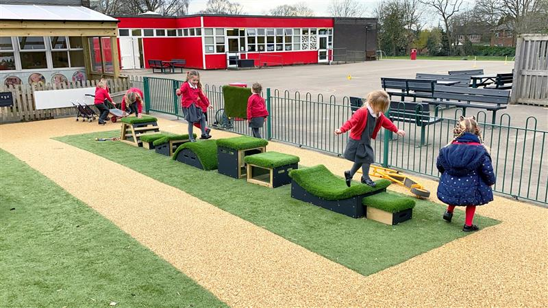 4 children playing on a set of get set go blocks in the playground