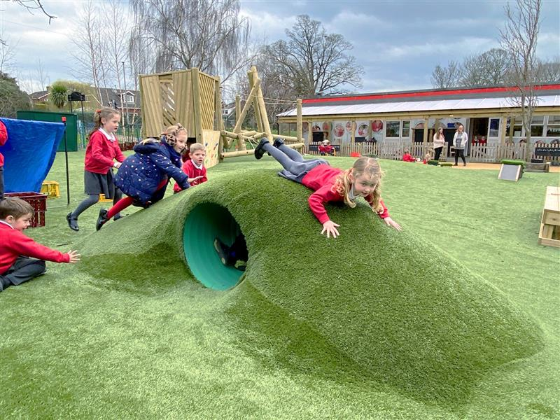 A child diving over the top of a playground mound with a tunnel underneath