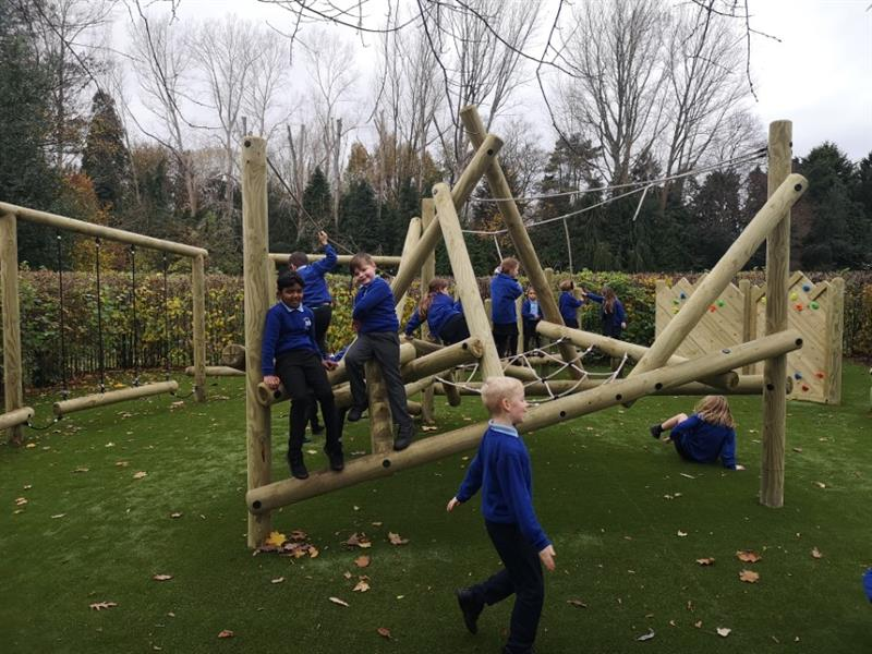 Children climbing on a pentagon play log and rope climbing frame