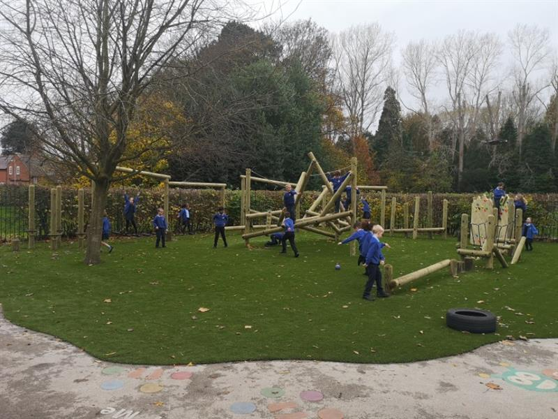 active playground equipment installed onto artificial grass surfacing