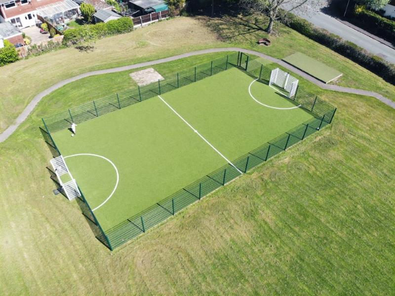 An astroturf muga pitch with white in-laid football markings and white goal ends