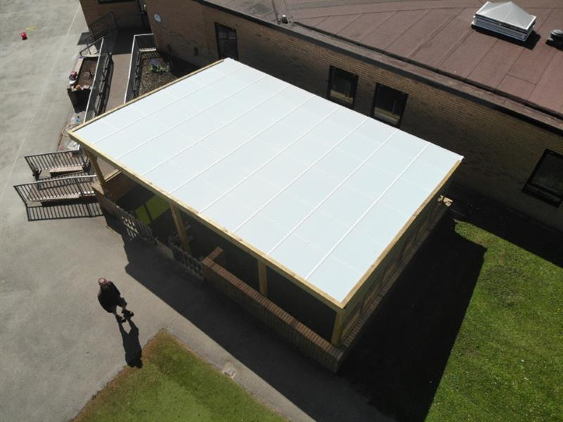 A timber canopy installed onto a school playground over artificial grass