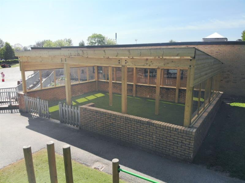 A timber canopy installed over the top of a brick wall to create an outdoor classroom