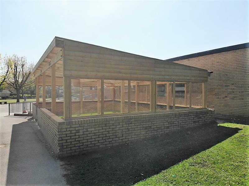 A timber canopy with glazed windows installed over a brick wall and artificial grass