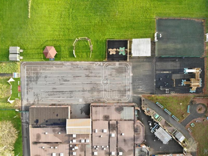 Aerial view of the school including their new playground equipment and sensory garden with a large field next to it.