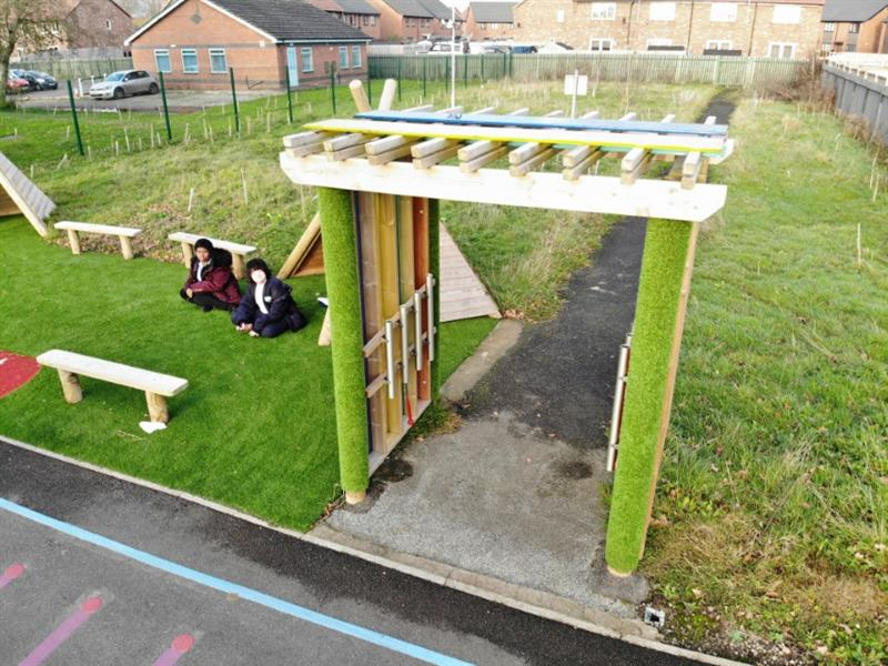 Aerial view of sensory arbour with 2 children wearing a maroon coat and a blue coat, sat on artificial grass in front of a wigwam and 3 benches in the sensory garden.
