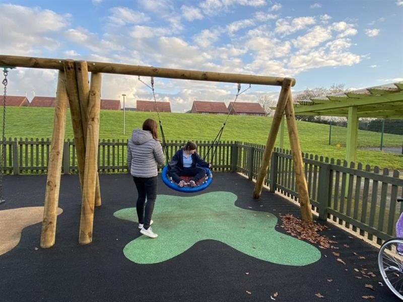 one child wearing a black coat sat in a basket swing with a teacher stood at the side pushing the child in the swing which has been installed onto wetpour surfacing in front of a large hill.