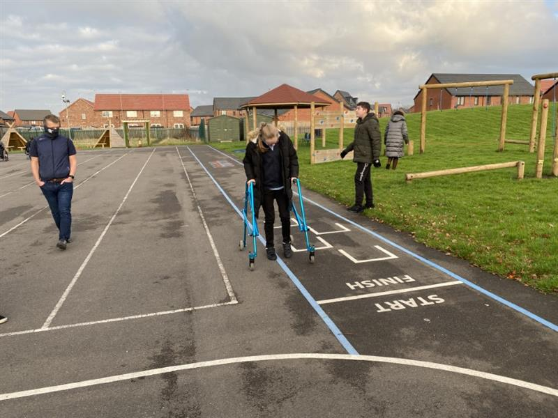 one child with a blue walking frame walking along the new playground markings with one teacher next to the school field which has new playground equipment installed onto it. Another child and teacher walking in the background.