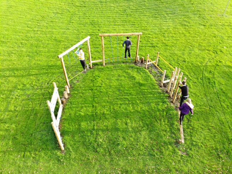 4 children, one wearing a bright purple coat playing on a U shaped trim trail which has been installed in the middle of a large field.
