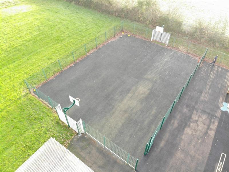huge muga pitch installed next to a large field with football nets and basketball nets above the football nets.