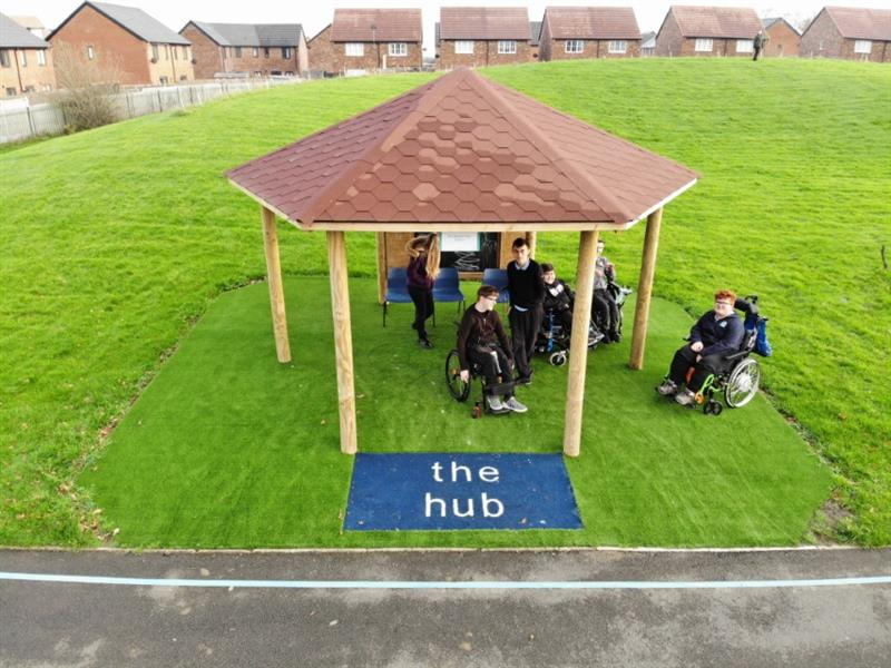 4 children in wheelchairs and 2 teachers underneath a gazebo with a chalkboard, which has been installed onto artificial grass at the front of a huge field with a blue surfacing sign saying the hub.