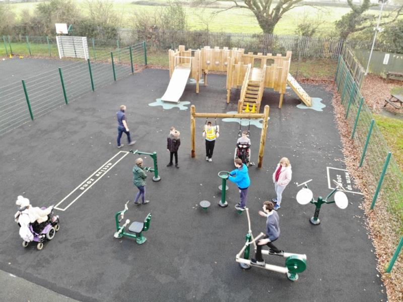 4 children playing on outdoor gym equipment with one child wearing a black coat stands and watches. 3 teachers supervising and one more child wearing a white coat is at the side sat in a wheelchair.