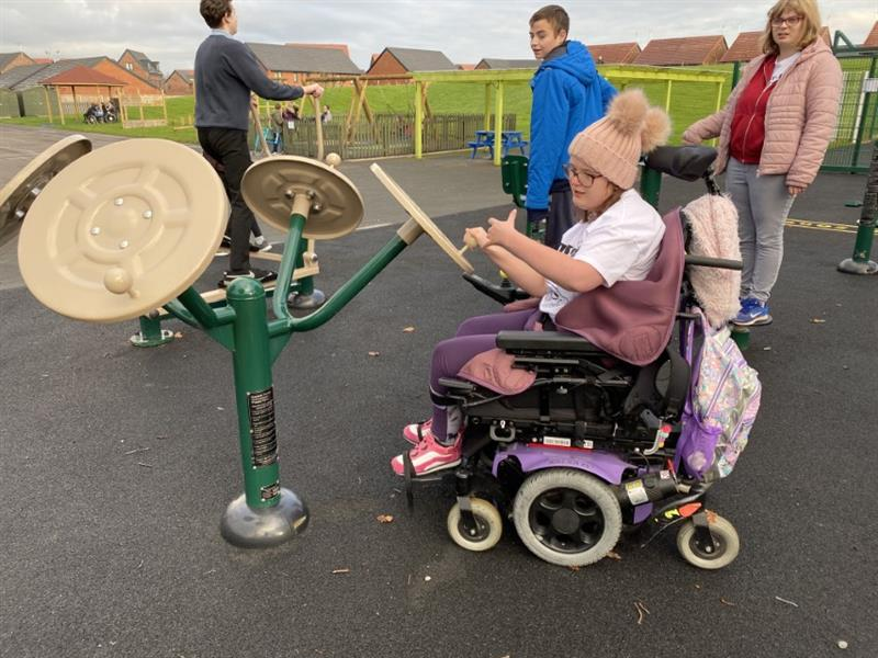 one girl wearing a pink pom pom wooly hat is sat in her wheelchair at the outdoor gym equipment using the equipment to build her arm muscles with one teacher watching close by and two boys playing in the background.