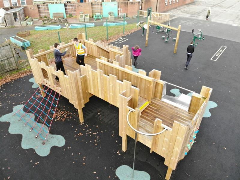 2 children, one wearing a yellow high vis jacket playing on a play castle that has a metal slide and fireman's pole with gym playground equipment installed next to the castle.