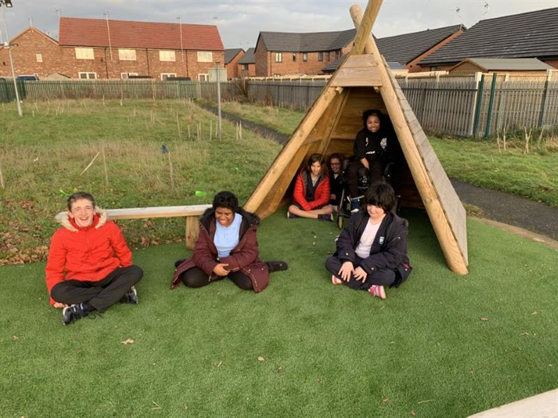3 children sat on artificial grass in front of a bench and a wigwam with more children sat inside of the wigwam which has been installed in front of a field with long grass.