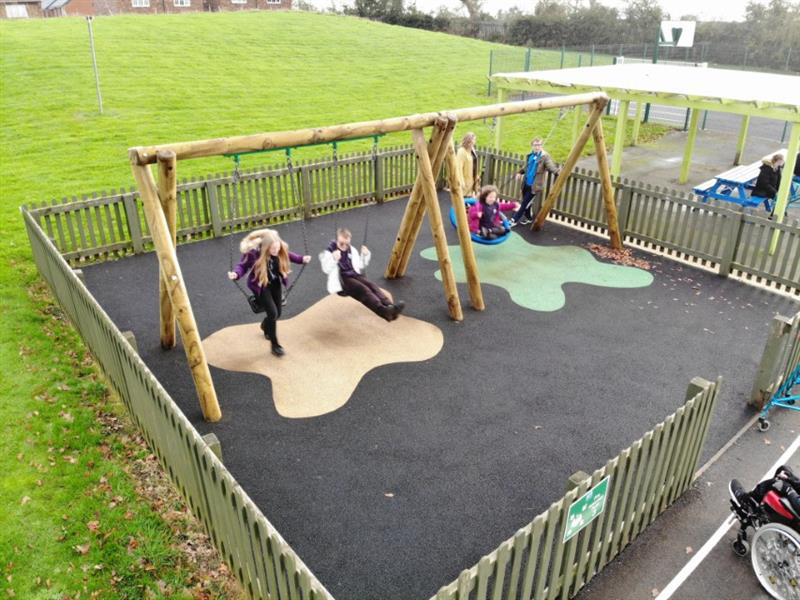 2 children one wearing a purple coat and one wearing a white coat playing on swings whilst another child wearing a pink coat swinging in a basket swing with two teachers stood at the side supervising the children.