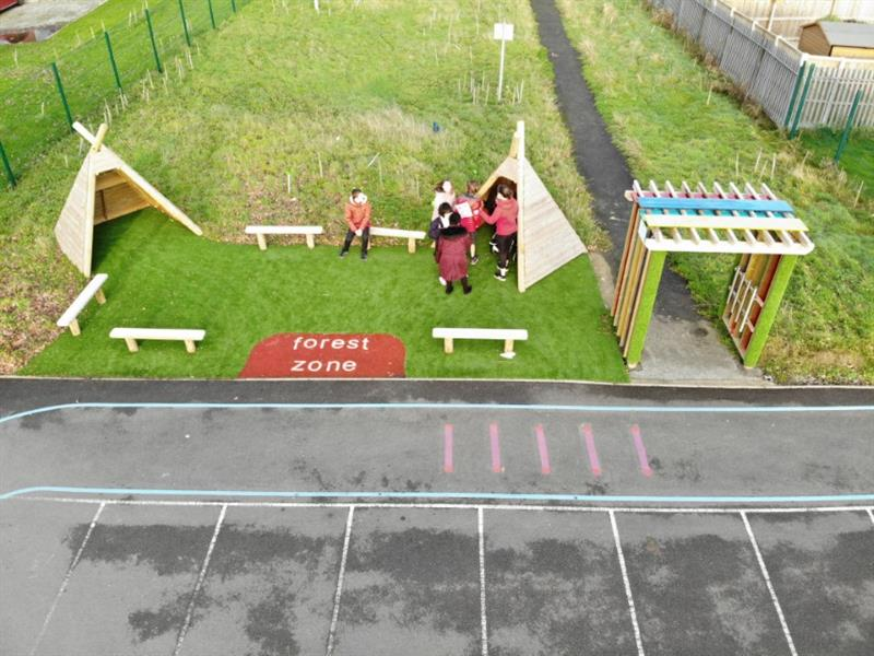 Aerial view of the sensory garden which includes two wigwams and 5 benches which have been installed onto the artificial grass with a sensory arbour installed next to the garden. 5 children are playing in front of one of the wigwams.