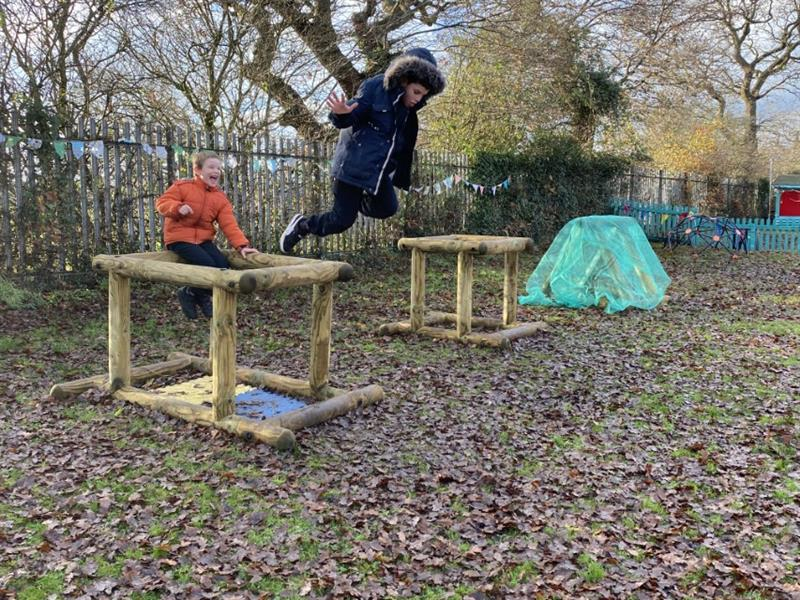 2 boys, one wearing an orange coat sat on a timber cube with one wearing a navy blue coat jumping off the timber cube onto the grass which is covered in brown leaves.