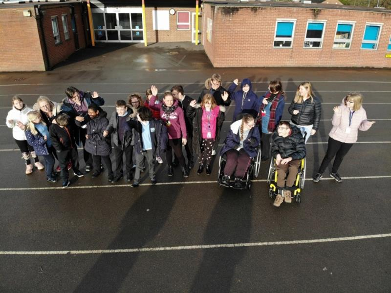 A class of children and teachers stood outside of the school building in the playground waving at the camera with two children in wheelchairs at the front of the group.
