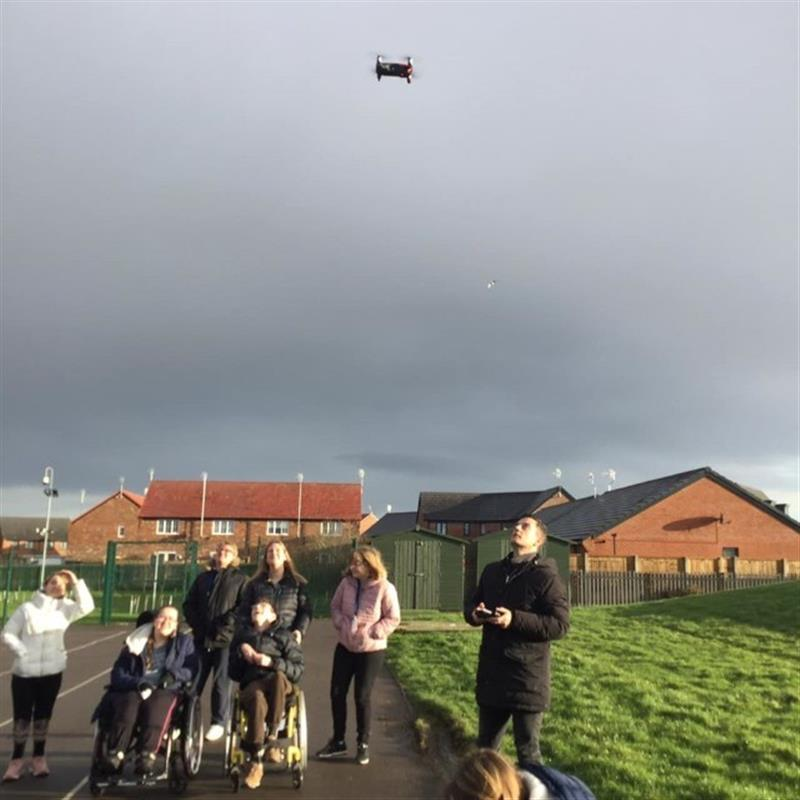 1 of our playground consultants showing children how he uses a drone to take pictures in front of the school field on the playground.