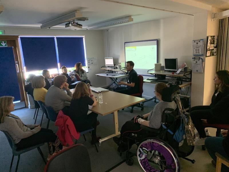 2 members of our products team delivering a careers talk in one of the school classrooms sat down in front of the whiteboard with one girl sat in a wheelchair that has purple wheels.