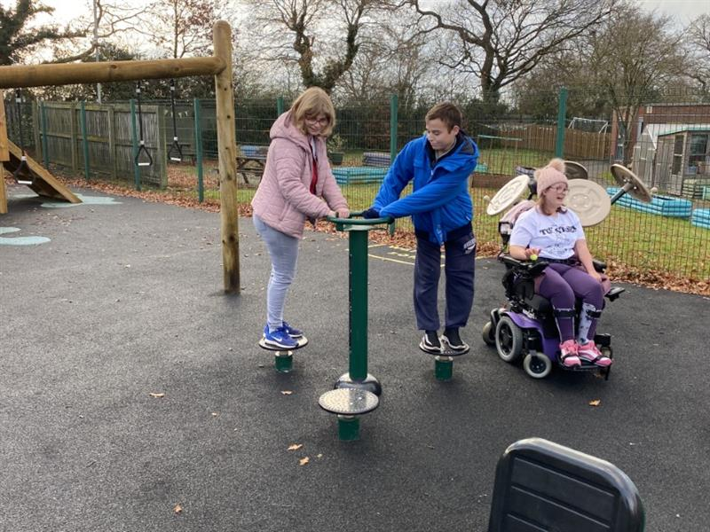 One teacher encouraging a boy to play on the gym equipment whilst one girl wearing purple trousers sits in her wheelchair next to the gym equipment smiling and laughing.