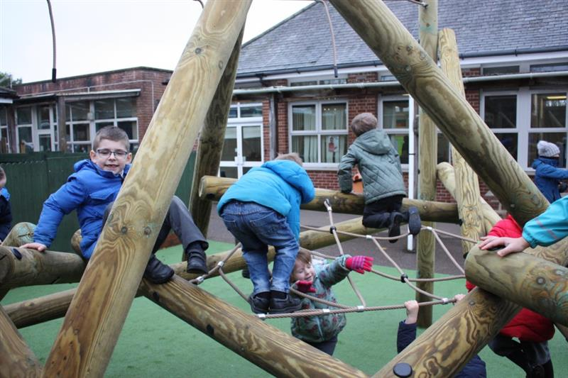 Children hanging on the ropes and balancing on the beams of a log climbing frame installed onto their school playground