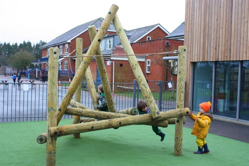 Harter Fell Climber installed onto Artificial Grass Surfacing with 2 reception children balancing on the lowest beam