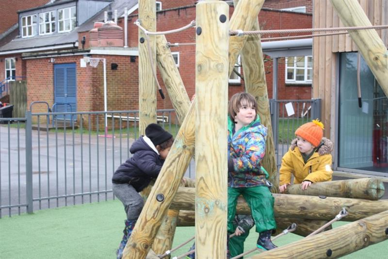 Harter Fell Climber installed onto Artificial Grass Surfacing with 3 reception children balancing on the beams