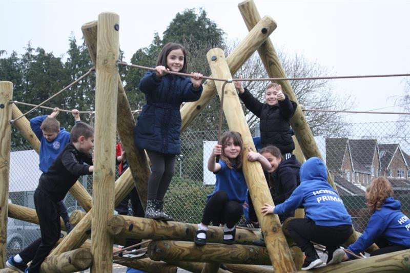 children playing on Pentagon Play's Tryfan Climbing Frame installed onto artificial grass on their school playground