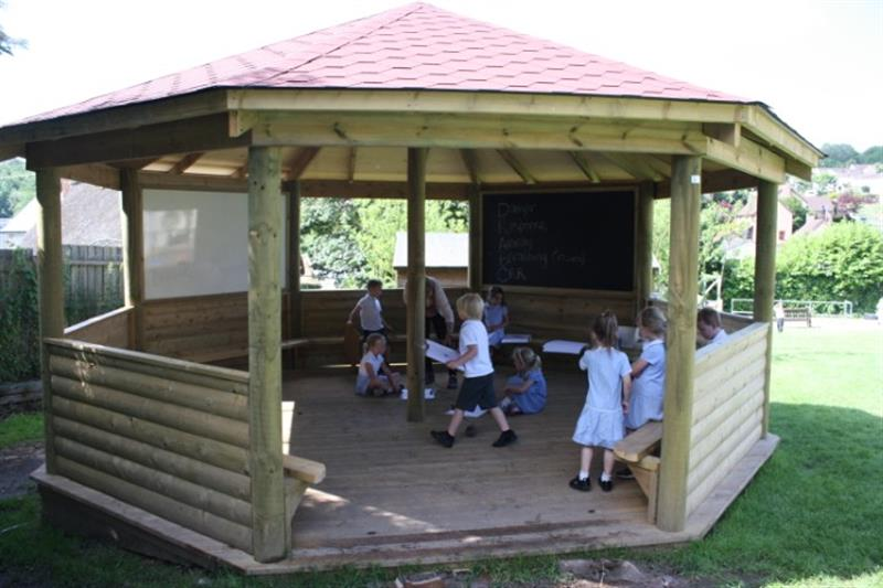 A group of children in an outdoor classroom participating in an outdoor lesson