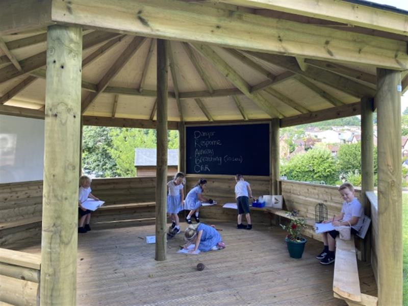 6 children sat in an outdoor gazebo participating a forest school session