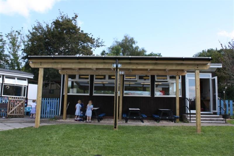 2 children stood under a timber canopy playing with loose play resources