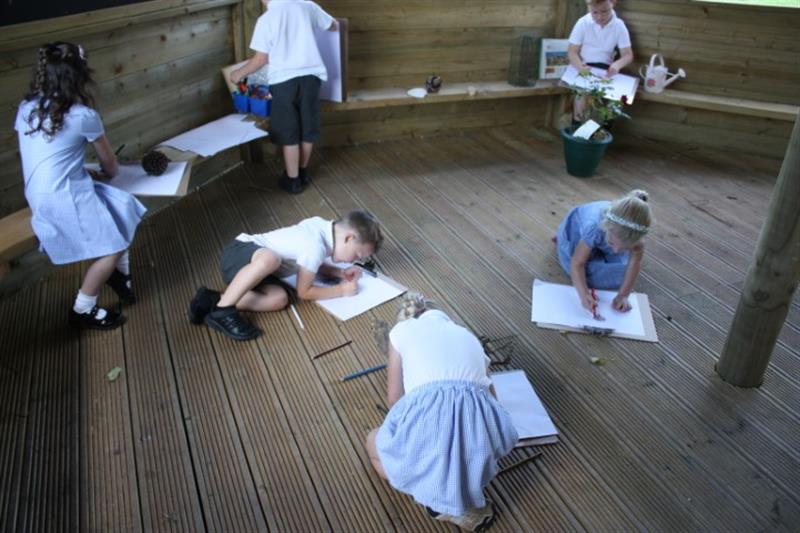 6 children sat on a gazebo base writing and drawing on paper