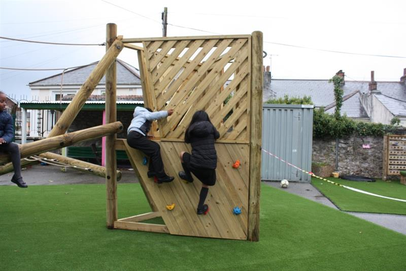 Children climbing on a log climbing frame