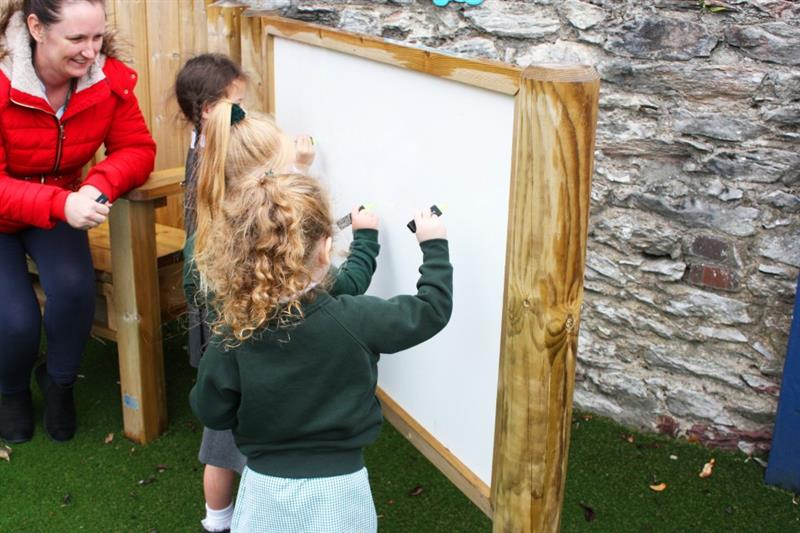 Child mark making on an outdoor giant whiteboard
