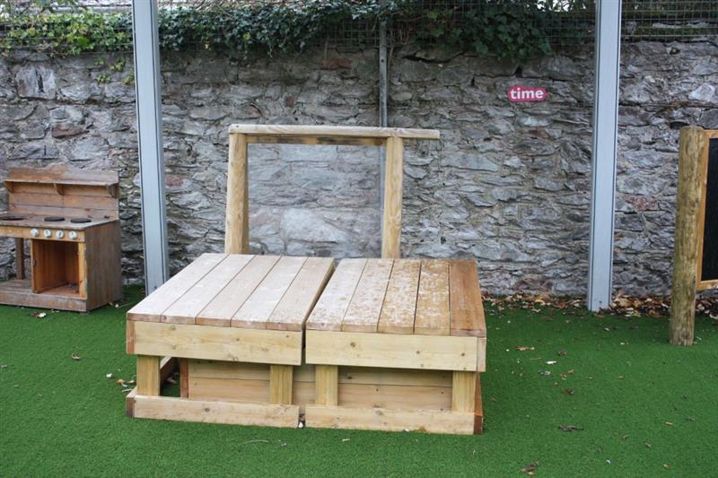 A covered sand box placed on top of artificial grass playground surfacing