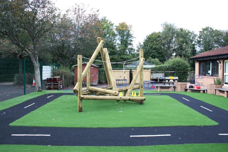 An eyfs climbing frame installed onto artificial grass