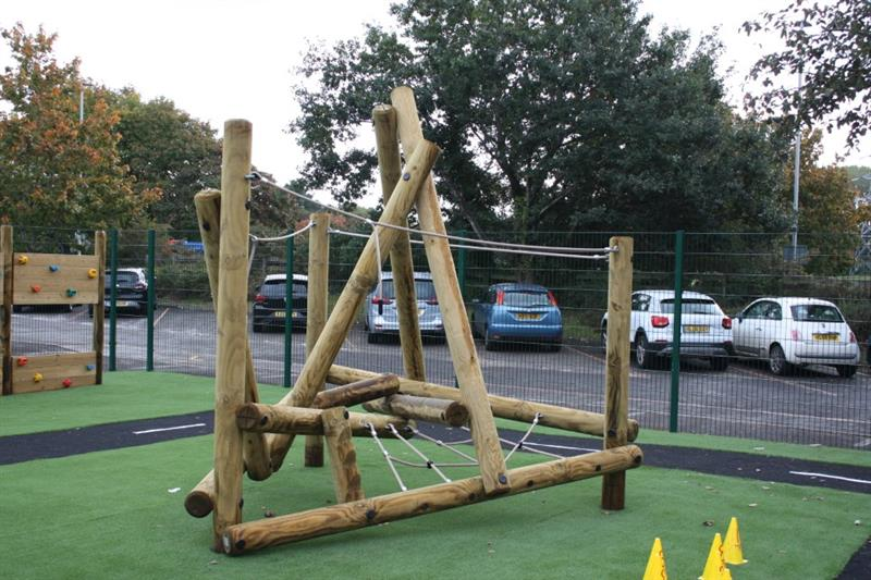 A log and rope climbing frame installed onto green artificial grass