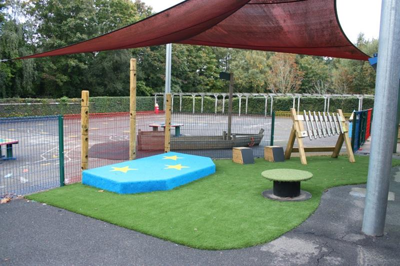 A performance stage and outdoor musical instruments installed onto artificial grass surfacing
